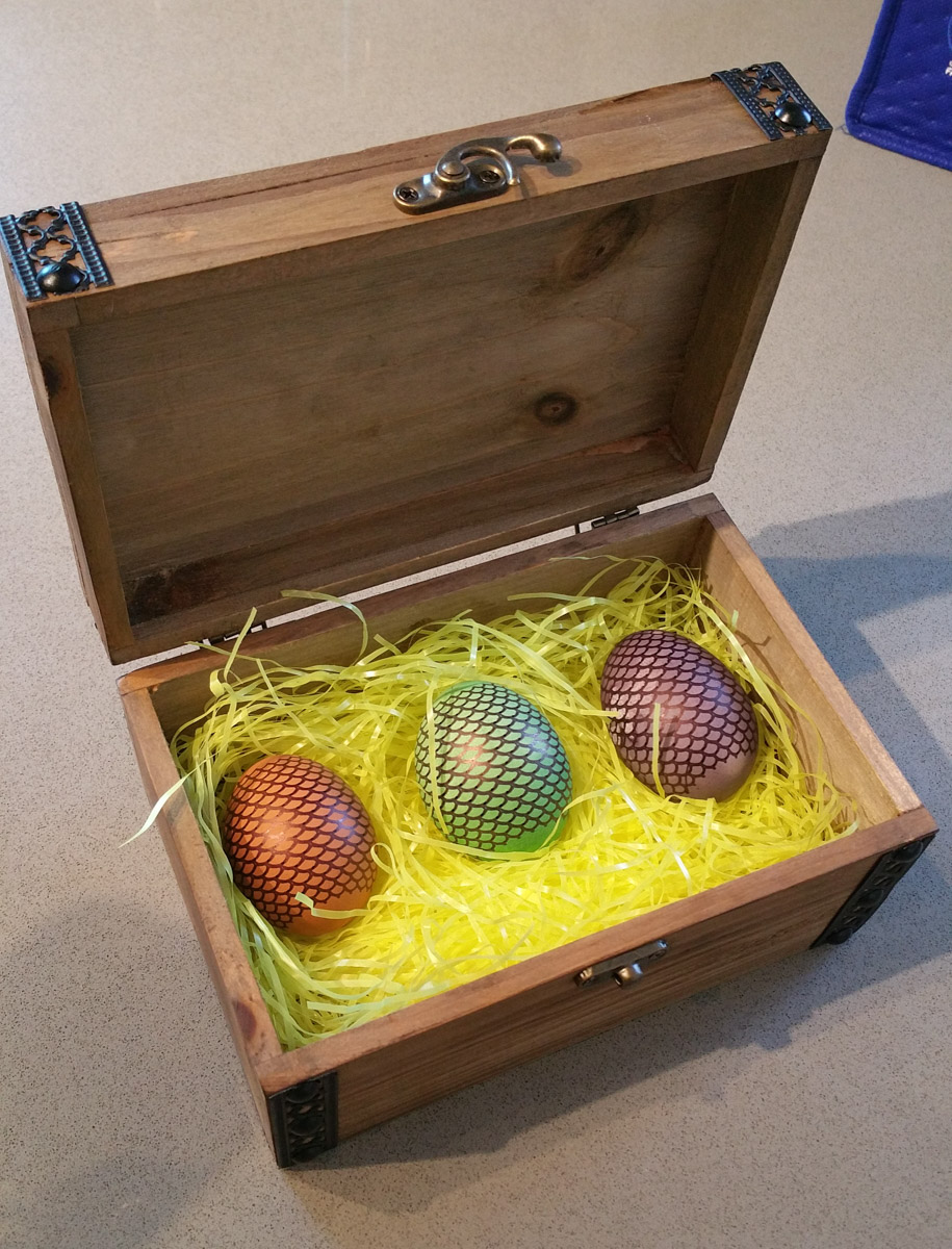 Three metallic scaly eggs in a wooden box