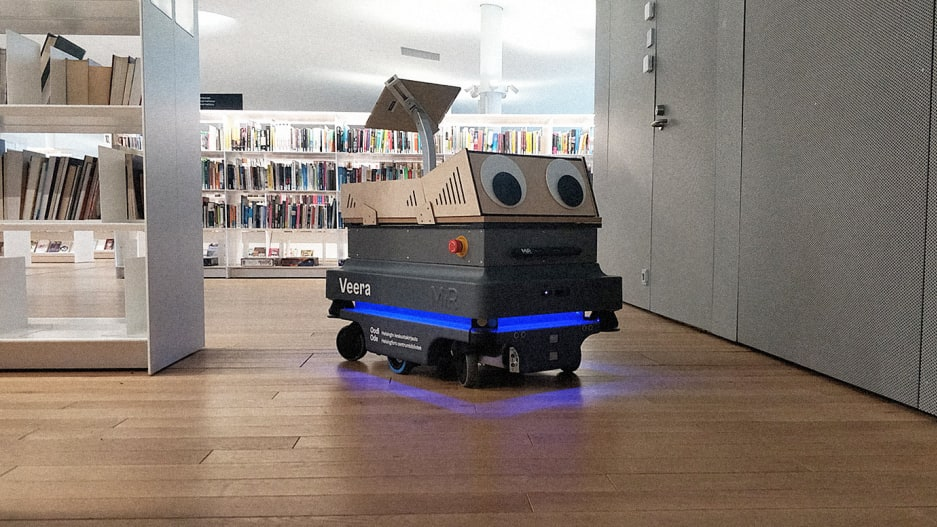 A googly eyed robot in a library