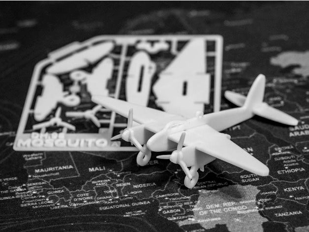 model airplane sitting on map next to sprue card of model parts